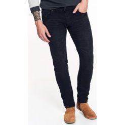 SPODNIE MĘSKIE JEANSOWE O KROJU SLIM. Niebieskie rurki męskie marki House, z jeansu. Za 89,99 zł.