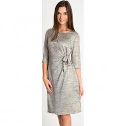 Szara sukienka z marszczeniem ze złotym połyskiem QUIOSQUE. Szare sukienki balowe marki QUIOSQUE, na karnawał, z dzianiny, z krótkim rękawem, mini, proste. W wyprzedaży za 119,99 zł.