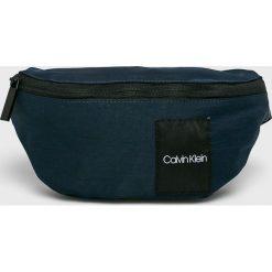 Calvin Klein - Nerka. Czarne walizki marki Calvin Klein, w paski, z materiału, małe. Za 229,90 zł.