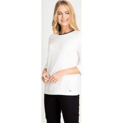 Biała bluzka z ozdobną lamówką QUIOSQUE. Białe bluzki asymetryczne QUIOSQUE, z jeansu, biznesowe. W wyprzedaży za 69,99 zł.
