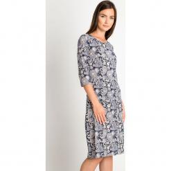 Granatowa prosta sukienka z orientalnym wzorem QUIOSQUE. Białe długie sukienki marki QUIOSQUE, na co dzień, na zimę, z nadrukiem, z dzianiny, klasyczne, z dekoltem na plecach, z długim rękawem, dopasowane. W wyprzedaży za 99,99 zł.