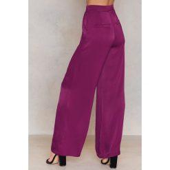 NA-KD Błyszczące spodnie z rozszerzanymi nogawkami - Purple. Fioletowe spodnie z wysokim stanem NA-KD, z wiskozy. W wyprzedaży za 60,89 zł.