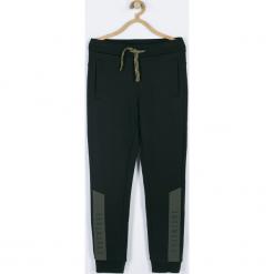 Spodnie. Czarne chinosy chłopięce TRAVELLER, z nadrukiem, z bawełny. Za 79,90 zł.
