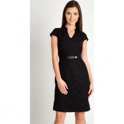 Czarna sukienka z błyszczącym wzorem QUIOSQUE. Czarne sukienki balowe marki QUIOSQUE, na karnawał, w paski, z tkaniny, z kopertowym dekoltem, z długim rękawem, mini, dopasowane. Za 219,99 zł.