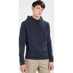 Calvin Klein KAMS FRENCH TERRY HOOD LOGO Bluza blue. Pomarańczowe kardigany męskie marki Calvin Klein, l, z bawełny, z okrągłym kołnierzem. W wyprzedaży za 384,30 zł.