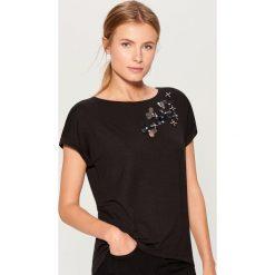 Koszulka z aplikacją - Czarny. Czarne t-shirty damskie marki Mohito, l, z aplikacjami. W wyprzedaży za 39,99 zł.