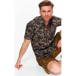 KOSZULA MĘSKA O DOPASOWANYM KROJU Z NADRUKIEM W MORO. Brązowe koszule męskie marki QUECHUA, m, z elastanu, z krótkim rękawem. Za 39,99 zł.