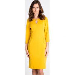 Żółta sukienka z dekoltem QUIOSQUE. Żółte sukienki balowe QUIOSQUE, do pracy, z dzianiny, z okrągłym kołnierzem, dopasowane. W wyprzedaży za 99,99 zł.