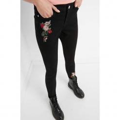 Jeansy z kwiatowym haftem. Czarne jeansy damskie skinny marki Orsay, z haftami, z bawełny. Za 99,99 zł.