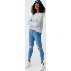 Jeansy skinny fit capri ze średnim stanem. Niebieskie jeansy damskie relaxed fit marki Pull&Bear. Za 79,90 zł.