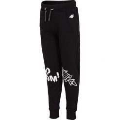 Spodnie dresowe dla małych chłopców JSPMD107 - GŁĘBOKA CZERŃ. Czarne spodnie chłopięce marki 4F JUNIOR, z nadrukiem, z bawełny. Za 39,99 zł.