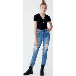 Jeansy mom fit z wysokim stanem i przetarciami. Niebieskie jeansy damskie relaxed fit marki Reserved. Za 109,00 zł.