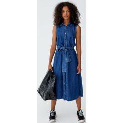 Sukienka koszulowa z wiązaniem. Niebieskie sukienki z falbanami marki Pull&Bear, z jeansu, z koszulowym kołnierzykiem, koszulowe. Za 109,00 zł.
