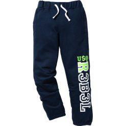 Spodnie dresowe z nadrukiem bonprix ciemnoniebieski. Niebieskie dresy chłopięce bonprix, z nadrukiem, z dresówki. Za 49,99 zł.