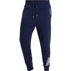 Spodnie dresowe męskie: New Balance ESSENTIALS GRAPHIC Spodnie treningowe pigment