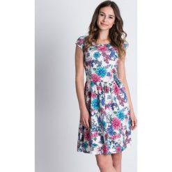 Rozkloszowana sukienka w kwiaty BIALCON. Białe sukienki hiszpanki BIALCON, na imprezę, na lato, w kwiaty, z zamszu, z kopertowym dekoltem, z krótkim rękawem, mini, kopertowe. Za 279,00 zł.