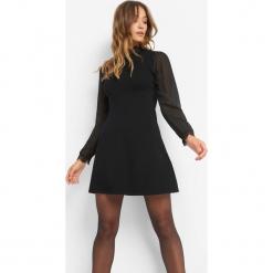 Sukienka z balonowymi rękawami. Czarne sukienki dzianinowe marki Orsay, xs, z dekoltem na plecach. Za 119,99 zł.