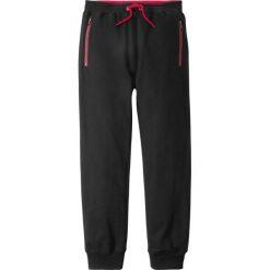 Spodnie dresowe z kieszeniami z zamkiem bonprix czarny. Czarne dresy chłopięce marki bonprix, z nadrukiem, z dresówki. Za 54,99 zł.