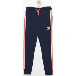 Spodnie dresowe z lampasami - Granatowy. Niebieskie dresy chłopięce marki Reserved, z dresówki. W wyprzedaży za 39,99 zł.