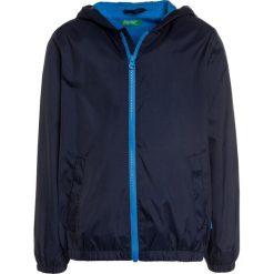 Benetton Kurtka przeciwdeszczowa dark blue. Niebieskie kurtki chłopięce przeciwdeszczowe marki Benetton, z materiału. Za 129,00 zł.