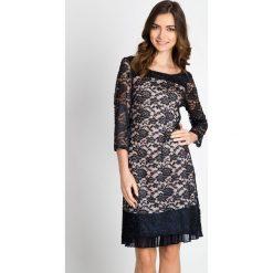 Koronkowa sukienka z plisami QUIOSQUE. Szare sukienki balowe marki QUIOSQUE, w koronkowe wzory, z koronki, z kopertowym dekoltem, z długim rękawem, dopasowane. W wyprzedaży za 139,99 zł.