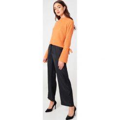 NA-KD Krótki sweter z wiązanym rękawem - Orange. Pomarańczowe swetry klasyczne damskie marki NA-KD, z dzianiny, z okrągłym kołnierzem. W wyprzedaży za 85,17 zł.