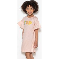 """Sukienka z błyszczącym napisem """"TOP"""", 3-12 lat. Czerwone bluzki dziewczęce bawełniane La Redoute Collections, z napisami, z okrągłym kołnierzem, z krótkim rękawem. Za 52,88 zł."""