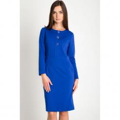 Niebieska taliowana sukienka z ozdobnymi guzikami QUIOSQUE. Niebieskie sukienki balowe marki QUIOSQUE, na zimę, s, z dzianiny, z dekoltem na plecach. W wyprzedaży za 139,99 zł.
