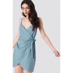 Kristin Sundberg for NA-KD Sukienka na ramiączkach z wiązaniem - Green. Zielone sukienki mini marki Kristin Sundberg for NA-KD, dekolt w kształcie v, na ramiączkach. W wyprzedaży za 48,59 zł.