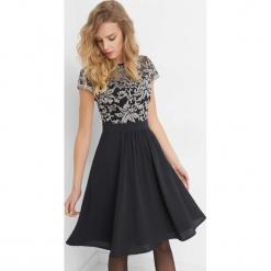 Rozkloszowana sukienka z haftem. Czarne sukienki koktajlowe marki Orsay, xs, z bawełny, z dekoltem na plecach. Za 159,99 zł.