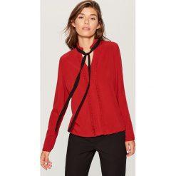 Koszula z kontrastowym wiązaniem - Czerwony. Czerwone koszule wiązane damskie marki Mohito, z kontrastowym kołnierzykiem. Za 89,99 zł.