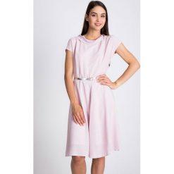 Sukienki hiszpanki: Pudrowa sukienka ze srebrnym paskiem QUIOSQUE