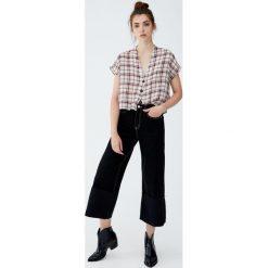 Krótkie jeansy z szerokimi nogawkami. Czarne jeansy damskie Pull&Bear. Za 109,00 zł.