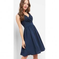 Rozkloszowana sukienka. Niebieskie sukienki koktajlowe Orsay, w koronkowe wzory, z elastanu, z kopertowym dekoltem, dopasowane. W wyprzedaży za 110,00 zł.
