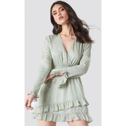 Linn Ahlborg x NA-KD Kopertowa sukienka - Green. Zielone długie sukienki marki Linn Ahlborg x NA-KD, z kopertowym dekoltem, z długim rękawem, kopertowe. Za 161,95 zł.