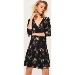Kopertowa sukienka z nadrukiem - Wielobarwn. Brązowe sukienki z falbanami marki Mohito, l, z kopertowym dekoltem, kopertowe. Za 79,99 zł.
