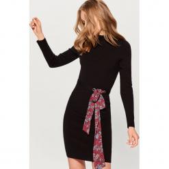 Obcisła sukienka z materiałowym paskiem - Czarny. Czerwone sukienki z falbanami marki Mohito, l, w koronkowe wzory. Za 139,99 zł.