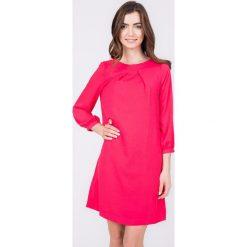 Malinowa trapezowa sukienka QUIOSQUE. Różowe sukienki na komunię marki QUIOSQUE, z materiału, z kopertowym dekoltem, kopertowe. W wyprzedaży za 59,99 zł.