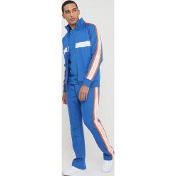 Calvin Klein Jeans SIDE STRIPE TRACK PANTS Spodnie treningowe royal blue. Niebieskie jeansy męskie marki Calvin Klein Jeans, z bawełny. W wyprzedaży za 494,10 zł.