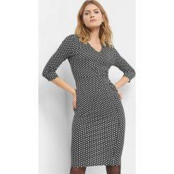 Dopasowana sukienka ze wzorem. Czarne sukienki dzianinowe marki Orsay, w geometryczne wzory, dekolt w kształcie v, dopasowane. Za 79,99 zł.