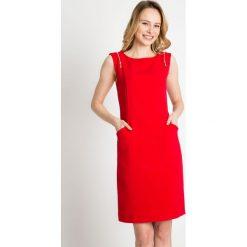 Czerwona sukienka z zamkami na ramionach QUIOSQUE. Czerwone sukienki dzianinowe marki QUIOSQUE, na spotkanie biznesowe, na lato, s, bez rękawów. W wyprzedaży za 79,99 zł.