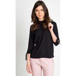 Elegancka czarna bluzka z wiązanymi rękawami  QUIOSQUE. Czarne bluzki wizytowe QUIOSQUE, z tkaniny, eleganckie, z dekoltem na plecach. W wyprzedaży za 69,99 zł.
