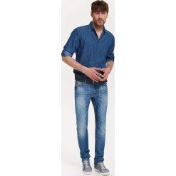 KOSZULA MĘSKA JEANSOWA Z NADRUKIEM I WYWIJANYMI RĘKAWAMI. Szare koszule męskie jeansowe marki Top Secret, na jesień, m, z nadrukiem. Za 69,99 zł.