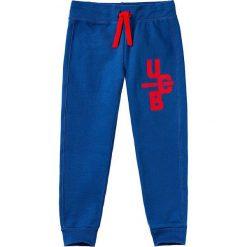 Spodnie dresowe w kolorze niebieskim. Niebieskie dresy chłopięce Benetton, z bawełny. W wyprzedaży za 29,95 zł.