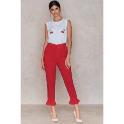 NA-KD Spodnie wykończone falbaną na nogawce - Red. Niebieskie spodnie z wysokim stanem marki NA-KD, z satyny. Za 161,95 zł.
