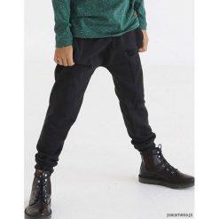 Spodnie dresowe z obniżonym krokiem. Czarne chinosy chłopięce Pakamera, w jednolite wzory, z dresówki. Za 79,00 zł.