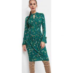 Dopasowana sukienka w kwiaty. Zielone sukienki dzianinowe Orsay, na lato, s, w kwiaty, ze stójką, dopasowane. Za 119,99 zł.
