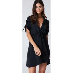 Sukienki: Kristin Sundberg for NA-KD Błyszcząca sukienka z dekoltem V – Black