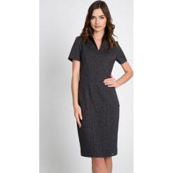 Grafitowa sukienka ze stójką QUIOSQUE. Szare sukienki balowe marki QUIOSQUE, do pracy, z dzianiny, ze stójką, z krótkim rękawem, mini, dopasowane. W wyprzedaży za 99,99 zł.