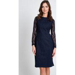 Granatowa sukienka z koronkowymi rękawami QUIOSQUE. Szare sukienki balowe QUIOSQUE, na sylwestra, w koronkowe wzory, z dzianiny, z kopertowym dekoltem, z długim rękawem, dopasowane. W wyprzedaży za 119,99 zł.